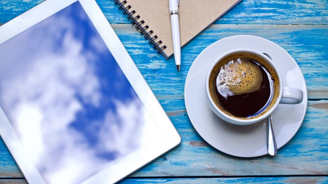 Coffee cup laptop notebook pen on wooden table